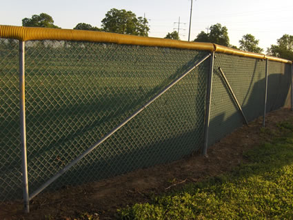cross bars on a baseball fence with a wind screen
